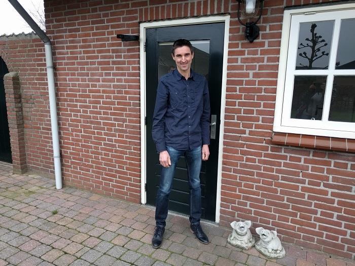 Varkensboer Jan Vermeer bij de achterdeur van zijn bedrijf